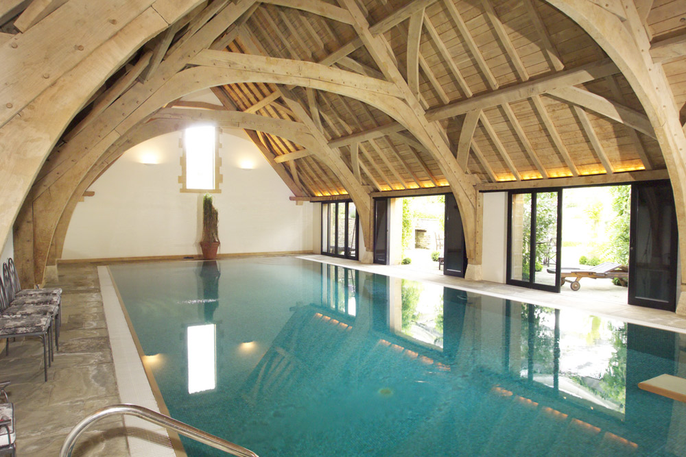 arch framed oak roof over swimming pool area