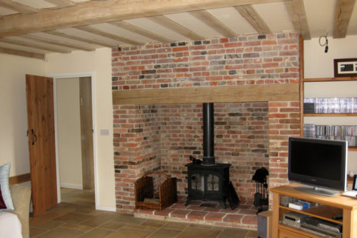 fireplace with exposed brick oak plynth and wood burner