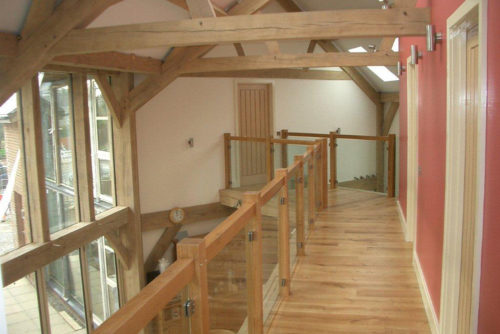 upper landing with exposed beams showing open bannister looking doen into family area