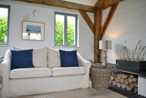 Oak frame home in Cornwall with a cosy corner in the open plan living area, showing sofa, windows, log basket and logs