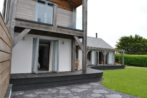 Exterior of an oak frame home in Cornwall with decking, garden, windows, doors and balcony